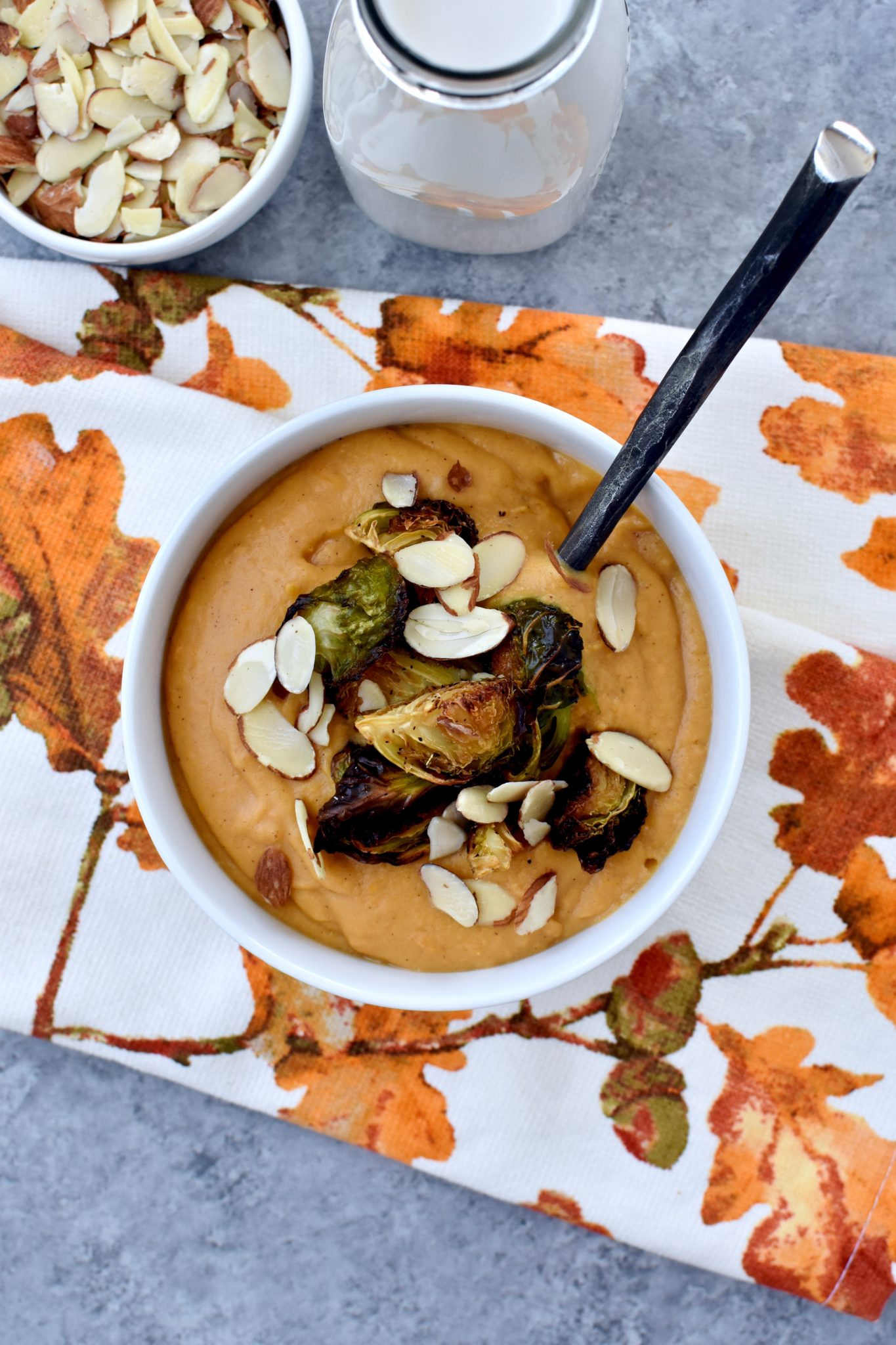 creamy sweet potato soup with roasted parmesan brussel sprouts and sliced almonds